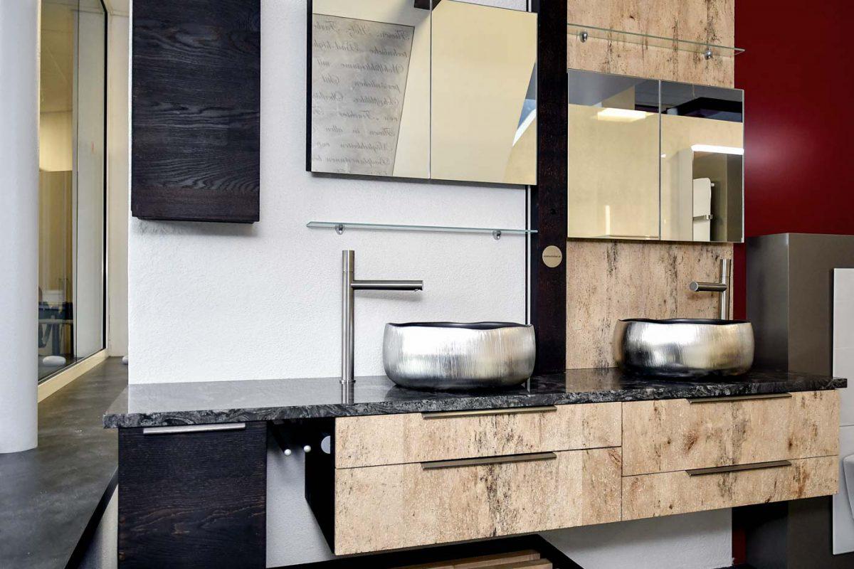 Badezimmer mit zwei Wasch-Schalen aus Metall und einer Holz-Front mit dunkler Steinplatte